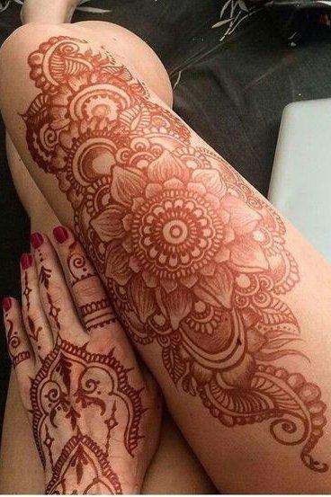 cute orange henna tattoo on thigh